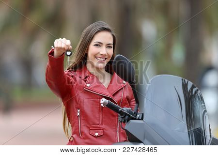 Happy motorcycle buyer showing keys at camera outdoor poster