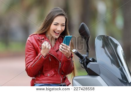 Excited Motorbiker On A Motorcycle Reading Good News Online In A Smart Phone