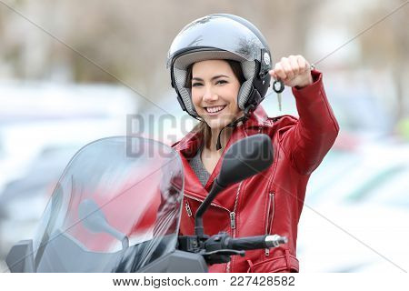 Happy Motorbiker Showing Keys Sitting On Her New Motorbike Outdoors On The Street