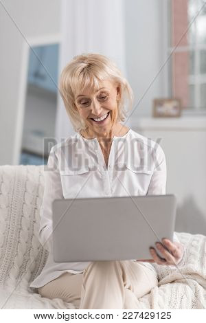 Advance Technology. Happy Appealing Mature Woman Using Laptop While Sitting And Staring At Screen