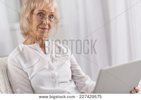 New Knowledge. Pleasant Tranquil Mature Woman Wearing Glasses While Spending Weekend And Looking At