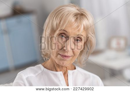 Pensive Mood. Portrait Of Earnest Pleasant Mature Woman Looking At Camera While Considering And Posi