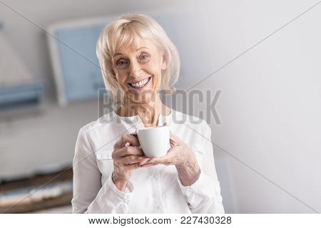 Morning Coffee. Jolly Merry Mature Woman Looking At Camera While Carrying Cup And Smiling