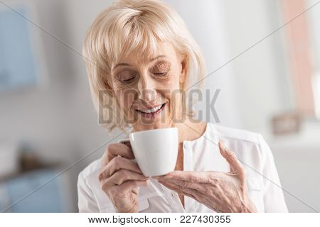 Doze Of Energy. Pensive Confident Mature Woman Staring Down While Holding Cup And Enjoying Life