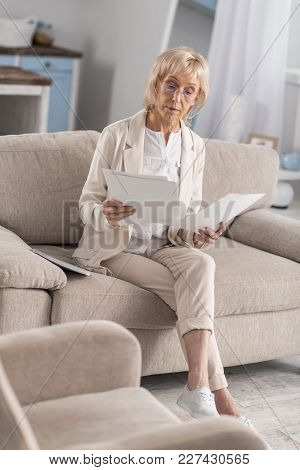 Experienced Businesswoman. Nice Charming Mature Businesswoman Working On Couch While Examining Paper