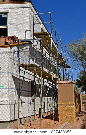 A Building Is Under Construction With Scaffolding And Tile Shingles On The Roof.