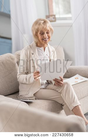 Precise Look. Positive Optimistic Mature Businesswoman Sitting On Couch While Carrying Papers And Sm