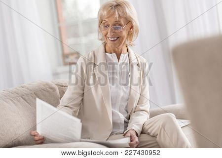 Business Task. Experienced Professional Mature Businesswoman Staring Down While Working With Papers