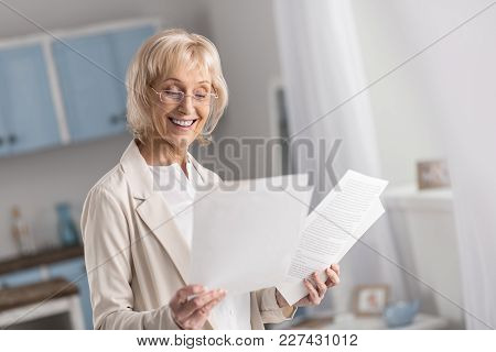 Always Working. Positive Joyful Mature Businesswoman Looking Down While Working With Documentation A