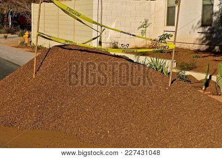 A Load Of Red Crushed Rock With Caution Tape  Lies On A Street For Future Yard Covering And Decorati