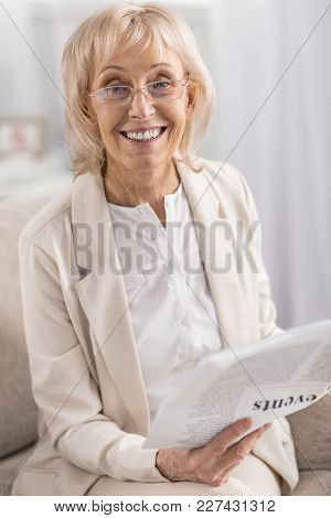 Interesting Article. Jolly Cheerful Mature Woman Grinning While Carrying Newspaper And Staring At Ca