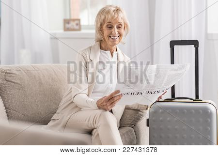 Business Trip. Attractive Appealing Mature Woman Waiting Near Suitcase While Scrutinizing Article An