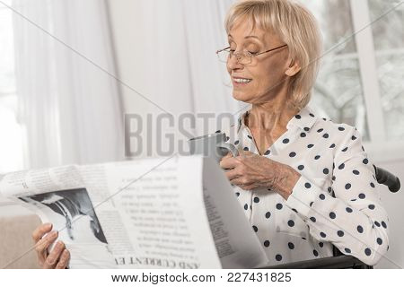 Advanced Laptop. Thoughtful Mature Disabled Woman Holding Cup While Looking At Newspaper And Wearing