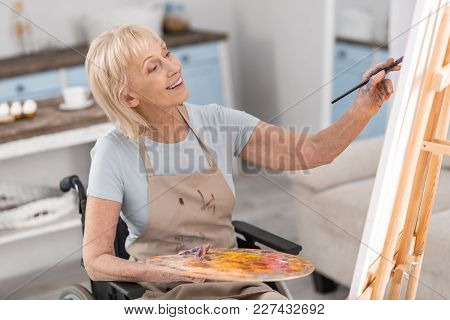 My Freedom. Handicapped Sincere Mature Woman Drawing In Wheelchair While Smiling And Using Tassel