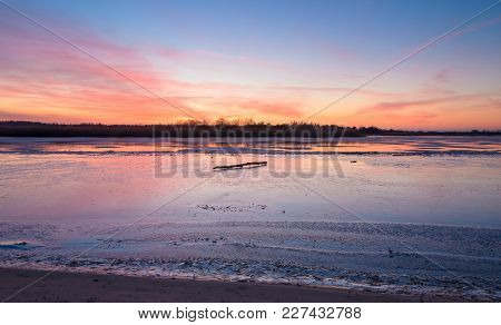 Bright Colorful Sunset Over The River  With Sky Reflection On Ice.