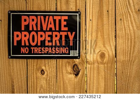 A Private Property Sign On A Tall Privacy Fence