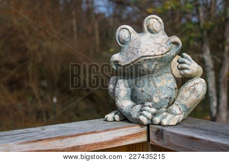 An Old Rustic Frog Sculpture Sitting On A Wooden Railing