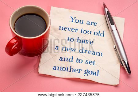 You are never too old to have a new dream and to set another goal - handwriting on a napkin with a cup of espresso coffee