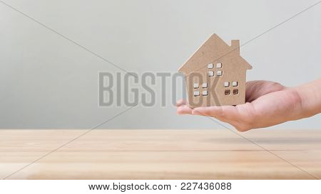 Property Investment And House Mortgage Financial Concept, Hand Holding Wooden Home