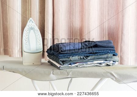 Ironing Clothes On Ironing Board,pile Of Clothes In The White Room.ironing Concept.