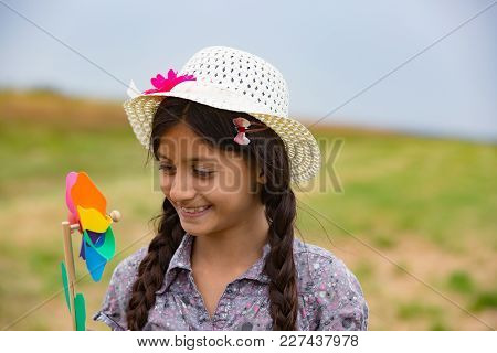 Smiling Girl With Strawhat And Pinwheel. Outdoor Shot.