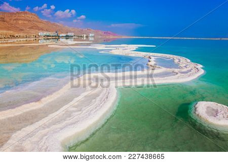 The concept of ecological and medical tourism. Very salty water glows with turquoise light. Reduced water in the Dead Sea, Israel