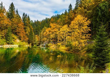 The reflections of forests in the lake. The quiet lake in Northern Italy, Lago de Fusine. Flood after rain. Concept of cultural and ecological tourism