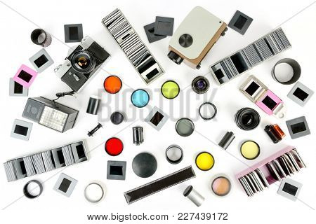 Top view of retro camera and slide projector with accessories isolated above white background. Flat lay