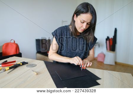 Sales Manager Working In Firm Dealing With Leather Products Making List Of Produced Bags, Wallets An