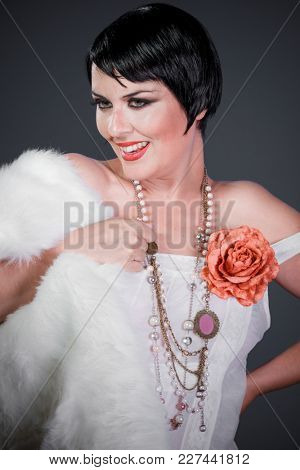 Brunette girl with short hair, French mane in the style of the 20s. She wears white fur coat and jewelry