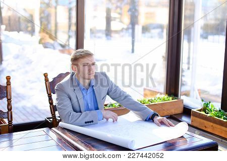 Student Of Architecture Faculty Sitting At Cafe Table And Looking At Drafting Work. Young Male Perso