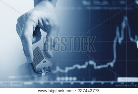 Hand Holding House, With Raising Graph Background. Real Estate Business And Investment In Real Estat