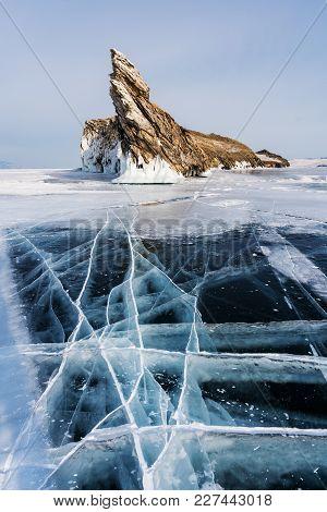Winter Landscape, Cracked Ground Of Frozen Lake Baikal With Beautiful Mountain Island On Frozen Lake