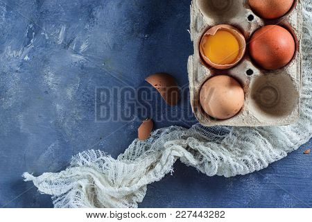 Broken Egg With Visible Yolk In A Carton. Close-up With Copy Space. Modern Easter Concept With Copy
