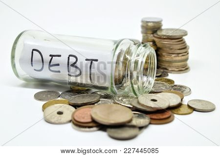 Debt Lable In A Glass Jar With Coins Spilling Out Isolated On White Background
