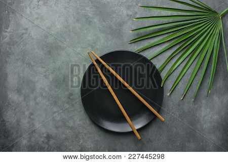 Black Empty Plate With Brown Bamboo Chopsticks Pal Tree Leaf On Dark Grey Stone Background. Asian Th