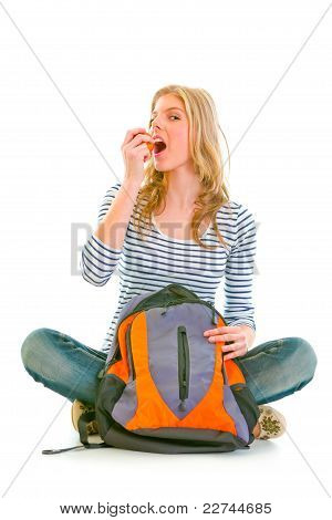 Pretty Girl Sitting On Floor With Schoolbag And Eating Apple