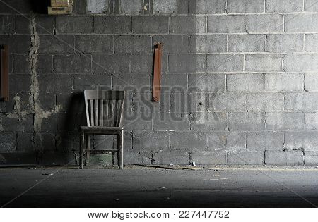 Abandoned Wooden Grey Chair Resting Against A Grey Concrete Block Wall In An Abandoned Carbide Graph