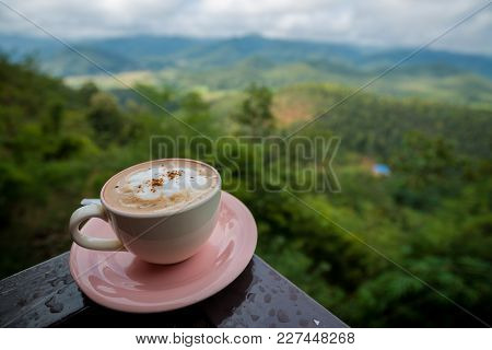 Coffee Latte In White Cup On Plate Stay On Porch With Mountain View And Cloudy Sky, Traveling In Tha