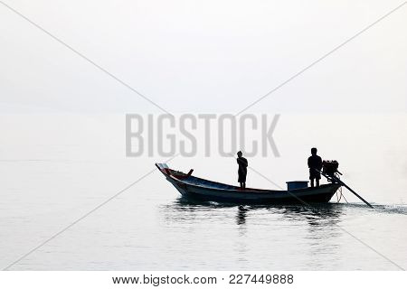 Silhouette Of The Long Tail Boat With Local People While Running In The Sea In Thailand