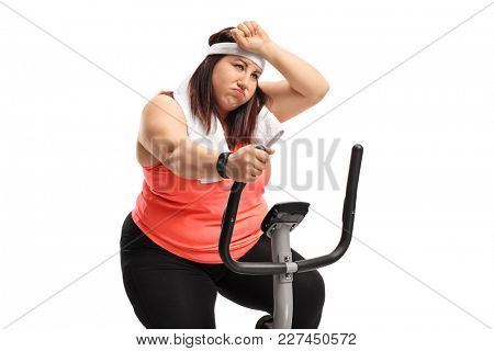 Tired overweight woman exercising on a cross-trainer machine isolated on white background