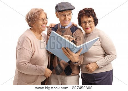 Two elderly women and an elderly man reading a book together isolated on white background