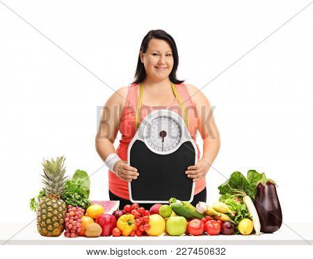 Overweight woman with a weight scale and a measuring tape behind a table with vegetables and fruit isolated on white background