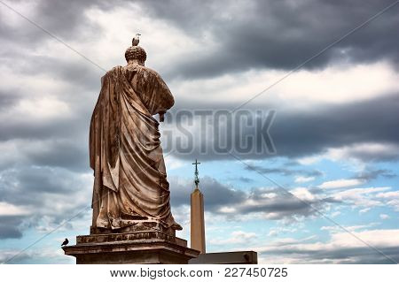 Vatican City, Vatican - May 17, 2017: The Back Of The Saint Peter Statue And The Obelisk Outside The