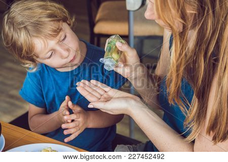 Mother And Son Using Wash Hand Sanitizer Gel In The Cafe.