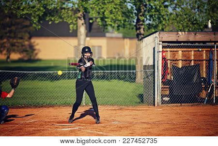 A Teenaged Girl Standing At Home Plate In A Black Baseball Uniform And Helmet Swinging A Bat At An I