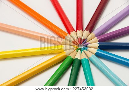 A Group Of Colored Pencils Folded In Rainbow Colors In A Circle On A White Background