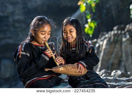 Daklak, Vietnam - Mar 9, 2017: Two Ede Ethnic Minority Little Girls Learning To Play The Flute In Fo
