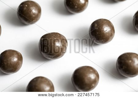 Malt balls with chocolate shot close up on a white background poster