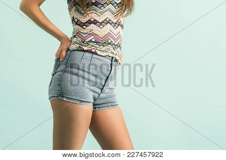Beautiful Woman Body In Denim Jeans Shorts On Green Background.